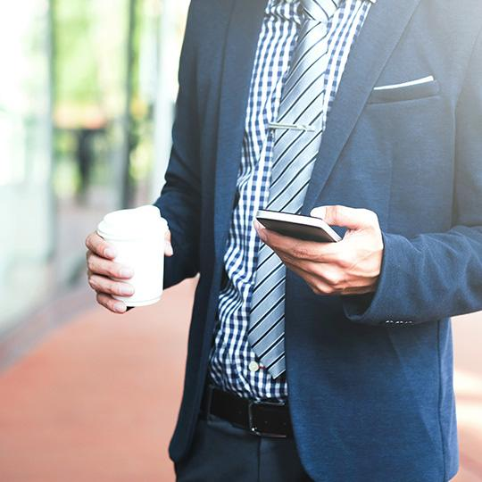 businessman holding a coffee and mobile phone
