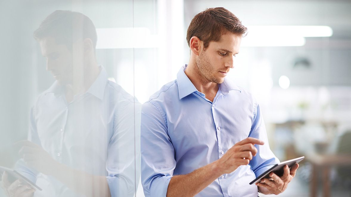 man standing by wall using tablet